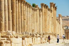 游人柱廊街道的参观废墟在古老罗马市Gerasa现代杰拉什在约旦 免版税图库摄影