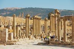 游人柱廊街道的参观废墟在古老罗马市Gerasa现代杰拉什在约旦 免版税库存图片