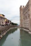 游人沿堤防走在S的Castello Scaligero墙壁附近 免版税库存照片