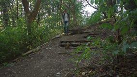 游人沿着走老残破的台阶在森林里 影视素材