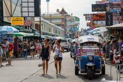 游人沿背包徒步旅行者避风港Khao圣路和tuktuk走在曼谷, 免版税库存照片