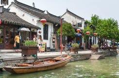 游人沿运河走在村庄 免版税库存照片