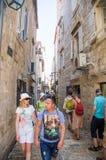 游人流程在老布德瓦狭窄的街道上的在黑山 图库摄影