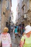 游人流程在老布德瓦,黑山狭窄的街道上的  免版税库存照片