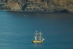 游人游艇在巨人的垂直的峭壁Acantilados de Los癸干忒斯峭壁的附近 从大西洋的看法 图库摄影