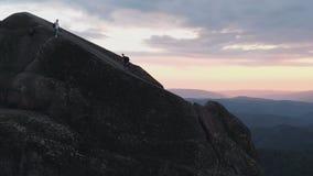游人的两个朋友空中射击攀登一个高岩石在日落 影视素材