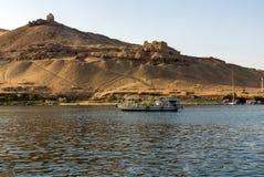 游人的小汽船尼罗河的在一个古老阿拉伯镇的背景废墟的开罗埃及,在沙漠 T 免版税图库摄影