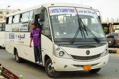 游人的旅馆服务公共汽车在镇街道上  免版税库存图片