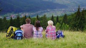 游人的朋友在一个美丽如画的地方在山的背景中坐 他们休息,敬佩美丽 免版税库存图片