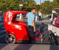 游人的红色人力车有法拉利在埃菲尔铁塔附近的汽车商标的在巴黎,法国 免版税库存图片