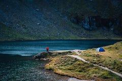 游人看法夫妇站立adove湖 冒险野营的旅游业和帐篷 在水附近的风景室外在Lacul Balea 免版税库存图片