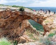 游人站立并且看Keshet洞-跨过一个浅洞的遗骸的与清扫v的古老自然石灰石曲拱 免版税库存照片