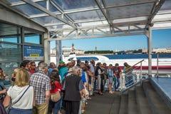 游人站立预期在码头的游船 免版税库存照片