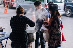 游人等待与小河的买的猪肉煮沸的米在一个大碗在食物市场上靠近Kew Mae平底锅在清迈,泰国 库存图片