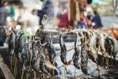 游人等待盐fishshioyaki烹调与一顿可口膳食 在冷气候 免版税库存照片