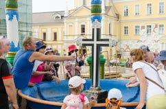 游人获取在碗的段落的圣水有一个十字架的在Svvyato三位一体St 免版税图库摄影