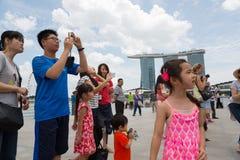 游人被拍摄反对新加坡背景  免版税库存图片