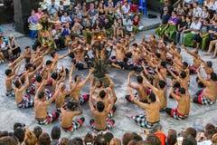 游人观看传统巴厘语Kecak舞蹈在巴厘岛的Uluwatu寺庙 免版税图库摄影