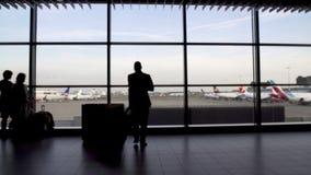游人走由巨大的终端视窗的,乘客剪影在机场 股票视频