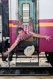 游人跌倒在火车外面 免版税库存照片