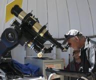 游人通过望远镜注视着太阳 免版税库存图片