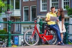 年轻游人结合看与自行车的地图 库存照片