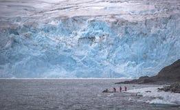游人去在冰和岩石的一艘橡皮艇 安德列耶夫 免版税库存照片