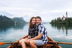 游人年轻夫妇木小船的在布莱德湖,斯洛文尼亚 免版税库存照片