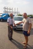 游人给施舍一个有胡子的人与帽子的乞求在停车场在入口城市 库存照片