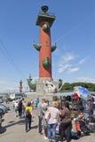 游人从有船嘴装饰的专栏选择纪念品在圣彼德堡 免版税图库摄影