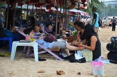 游人从泰国妇女接受在Pataya海滩的按摩 免版税库存图片