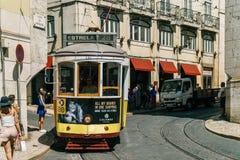 游客旅行在历史的电车之前在街市里斯本市 免版税库存图片
