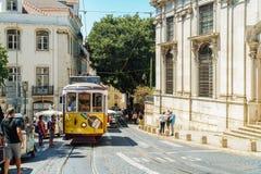 游客旅行在历史的电车之前在街市里斯本市 免版税库存照片
