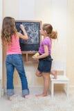 游戏室油漆的小女孩在黑板 图库摄影