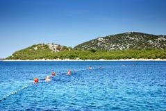 游泳与浮体的人们在干净,温暖的海,克罗地亚达尔马提亚 免版税库存照片