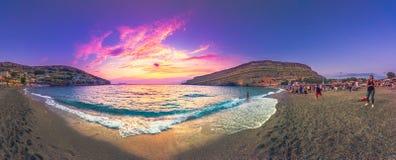 游泳和使用在海的愉快的人民剪影在日落,关于获得乐趣的概念在海滩 免版税库存照片