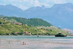 游泳和晒日光浴在湖前面洛桑的人们 免版税图库摄影