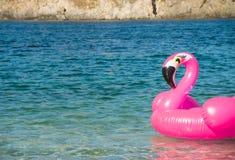 游泳圆环以在水的一群桃红色火鸟的形式在海滩附近,水背景 花梢游泳圆环 使布赖顿椅子日甲板英国节假日懒人海边有风夏天的星期日靠岸 免版税库存图片