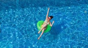 游泳圈子的愉快的年轻性感的妇女在游泳池 免版税库存照片