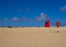 游泳圈子 在海滩的救生圈红颜色有明亮的沙子和天空背景 两个警报信号 安全卫兵 库存图片