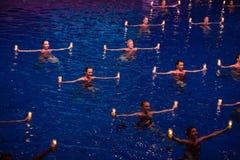 游泳在与蜡烛的水池的女孩在展示奥林匹克冠军 库存图片