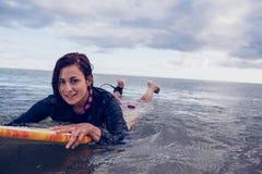 游泳在冲浪板的妇女的画象在水中 免版税库存照片