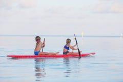 游泳在冲浪板的小逗人喜爱的女孩在期间 免版税库存照片