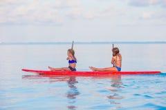 游泳在冲浪板的小逗人喜爱的女孩在期间 免版税库存图片