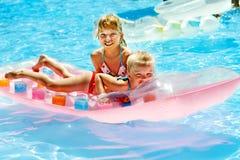 游泳在可膨胀的海滩床垫的孩子 免版税图库摄影