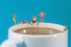 游泳在咖啡的塑料人民 库存照片