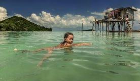 游泳在她的木房子,沙巴Semporna,马来西亚附近的Semporna海村庄的Bajau部落小女孩 免版税库存图片