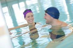 游泳在室内游泳池的夫妇游泳者 免版税库存照片