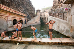 游泳在山的神圣的水中的人们 库存照片