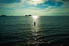 游泳在日落的海 图库摄影